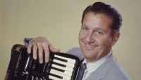 Lawrence Welk (1903-1992), US musician and band leader, smiling while posing with an accordian, circa 1955