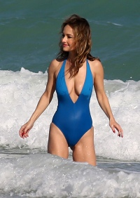 Famous Chef Giada DeLaurentiis laughs off a wardrobe malfunction in a very low cut swimsuit as she takes a dip in Miami during South Beach Wine & Food Festival