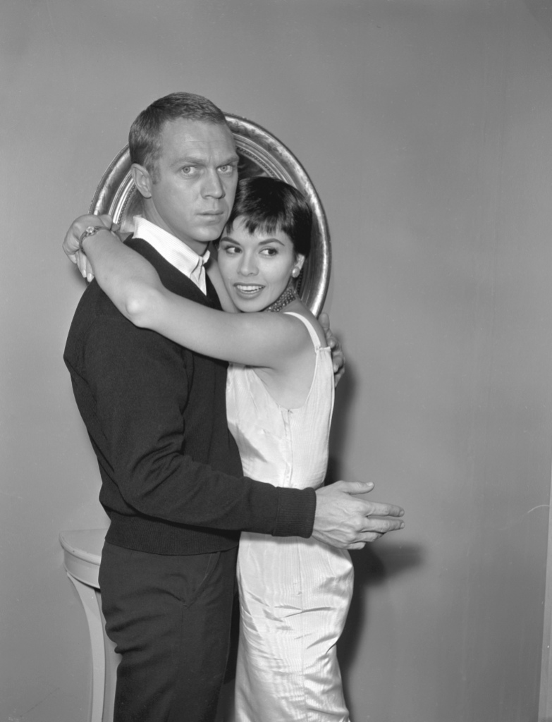 Married American actors Steve McQueen (1930 - 1980) and Neile Adams embrace during the filming of an episode of the television anthology series 'Alfred Hitchcock Presents' entitled 'Man from the South,'