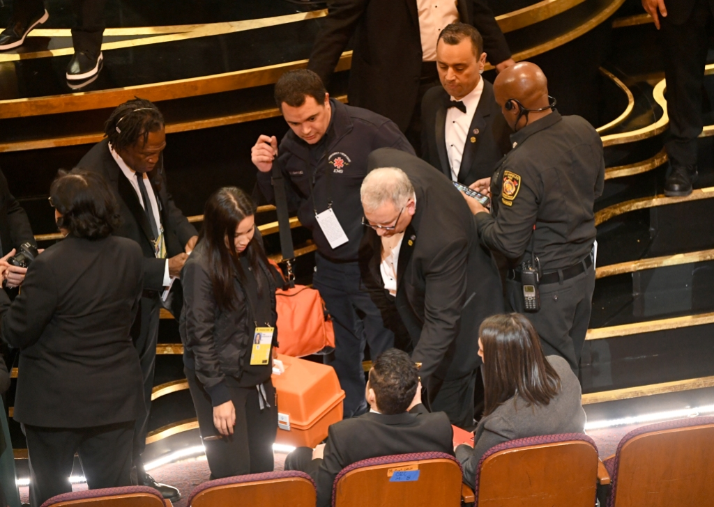 An EMT (standing, center) speaks with Rami Malek (seated, center) during the 91st Annual Academy Awards