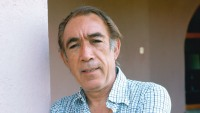 Anthony Quinn (1915-2001), poses with his arms folded across his chest, wearing a blue-and-white short-sleeved shirt, circa 1975.
