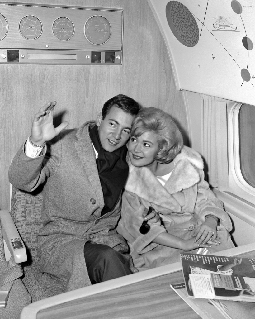 Bobby Darin, 24, the young man with the swinging tones, cuddles up to his bride, actress Sandra Dee, 18, as they fly out of International Airport for Hollywood honeymoon