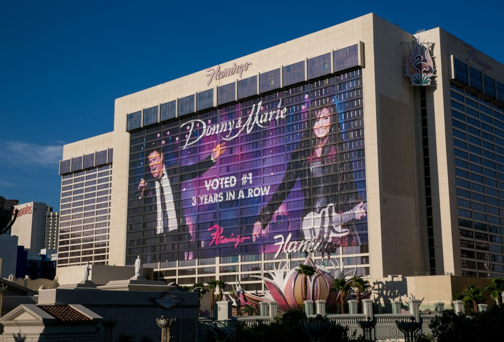 A large billboard promoting the Donny & Marie Osmond show on the side of the Flamingo Hotel at the corner of Flamingo Road and Las Vegas Blvd