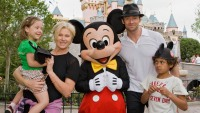 Actor Hugh Jackman, his wife Deborra Lee Furness, and children Oscar Jackman and Ava Jackman pose with Mickey Mouse outside Sleeping Beauty Castle at Disneyland