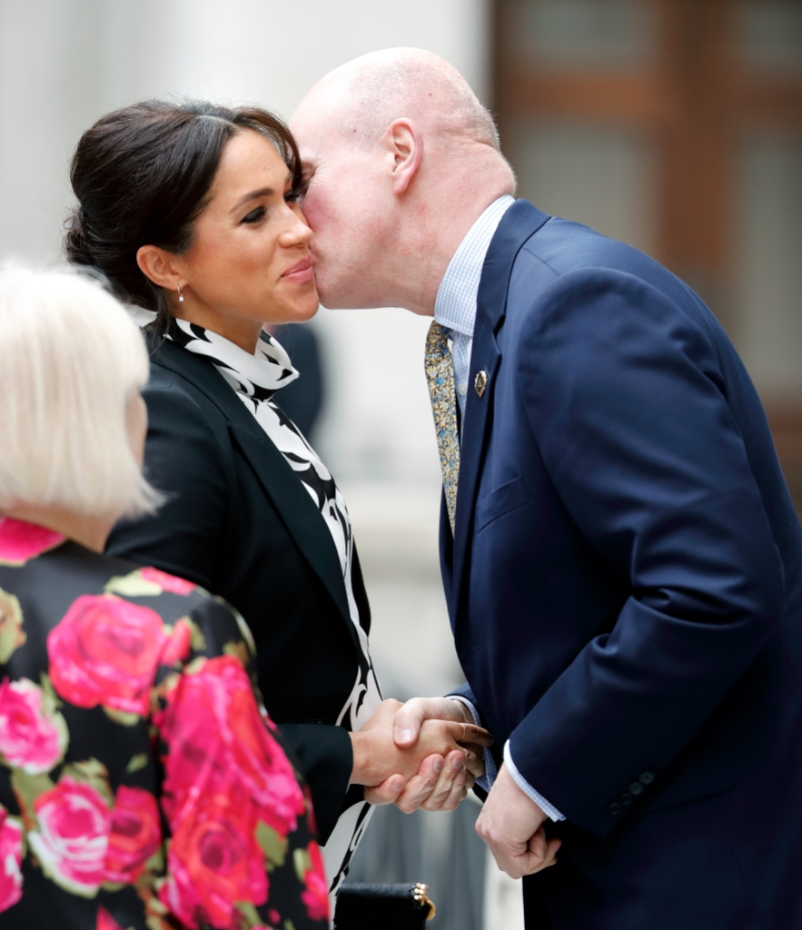 Meghan Markle, Duchess of Sussex kisses Lord Christopher Geidt (former Private Secretary to Queen Elizabeth II) as she arrives to attend a panel discussion, convened by The Queen's Commonwealth Trust, to mark International Women's Day