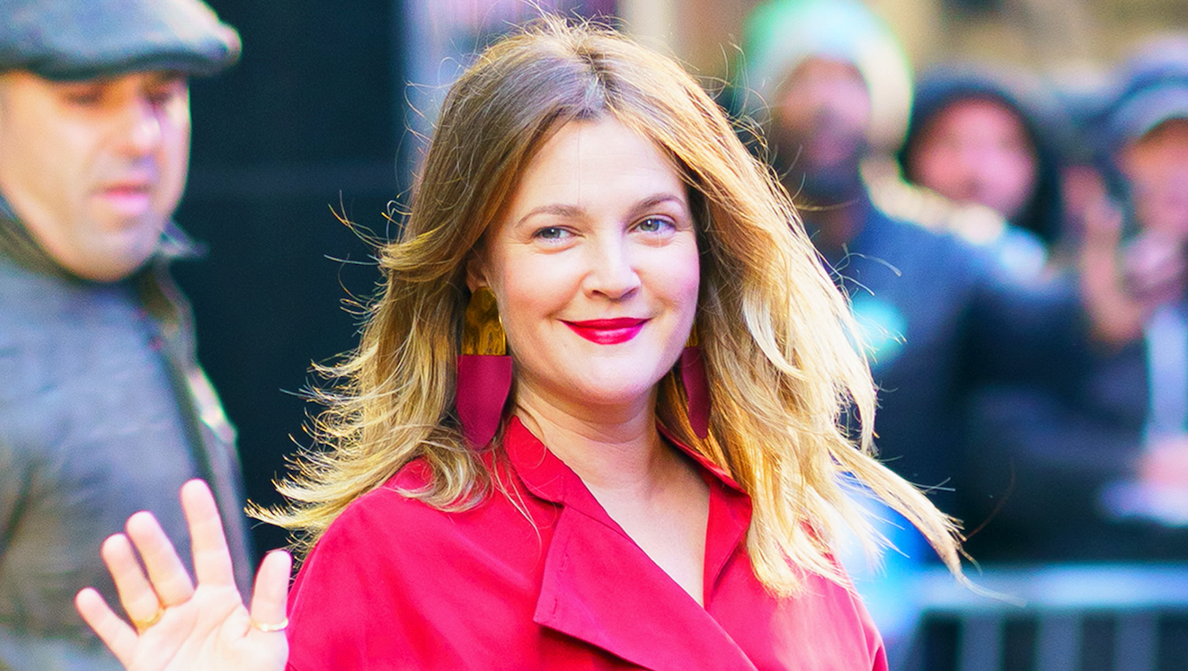 Drew Barrymore waving outside of Good Morning America NYC wearing a red pantsuit.