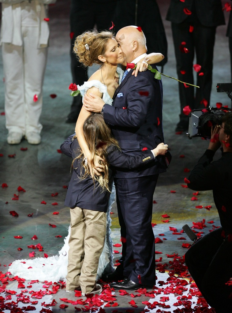 """Singer Celine Dion is embraced by her husband and manager Rene Angelil and their son Rene-Charles Angelil after the final performance of her show """"A New Day..."""" at The Colosseum at Caesars Palace"""