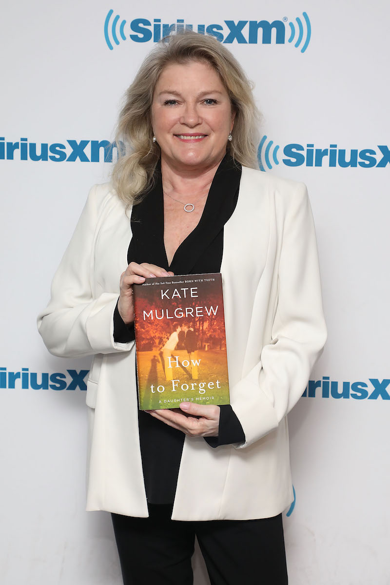 Kate Mulgrew holding the book 'How to Forget'