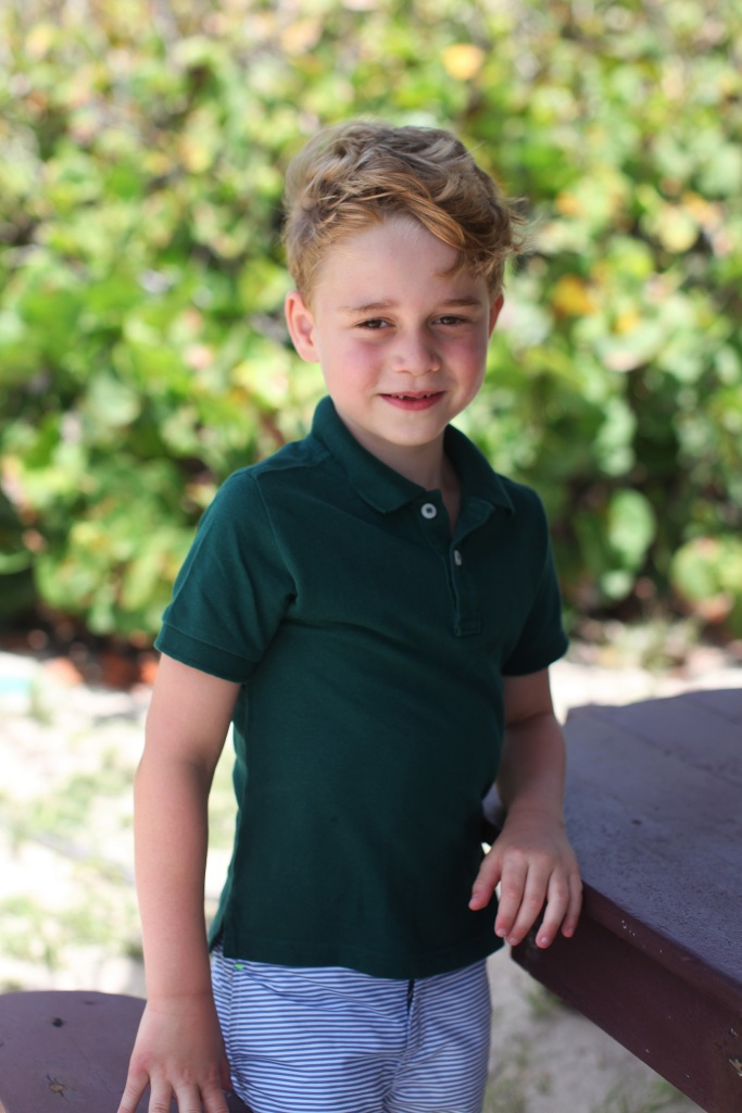 prince george wears green polo shirt and blue and white striped pants in portrait taken by kate middelton