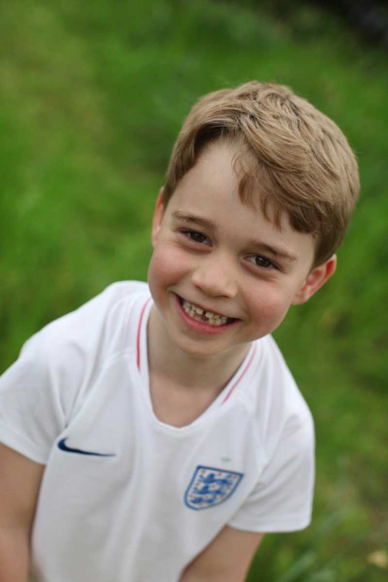 prince george smiles wearing a white soccer tee in the garden at kensington palace