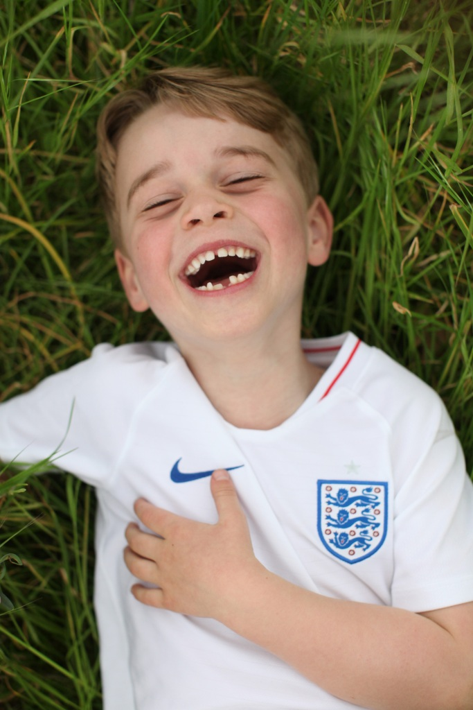 prince george lays in the grass laughing in the garden at kensington palace