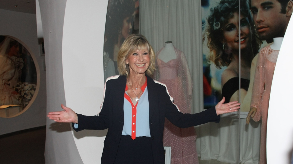 Olivia Newton-John Smiles as She Arrives to an Exhibition Showcasing Her Clothes