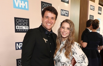 bindi irwin wears a white dress with black print while her fiance chandler powell wore a black shirt, black blazer and khaki pants at the Critics' Choice Real TV Awards 2019 bindi irwin will honor late father steve at wedding