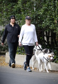 KISS frontman Gene Simmons is seen dressed in a backwards cap, black sweatpants and a matching top as walks his two dogs, George and Baby, with his wife, former Playboy playmate of the year, Shannon Tweed.