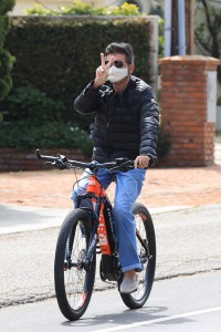 Simon Cowell and Lauren Silverman sport masks during bike ride