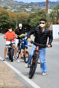 Simon Cowell and Lauren Silverman sport masks during bike ride